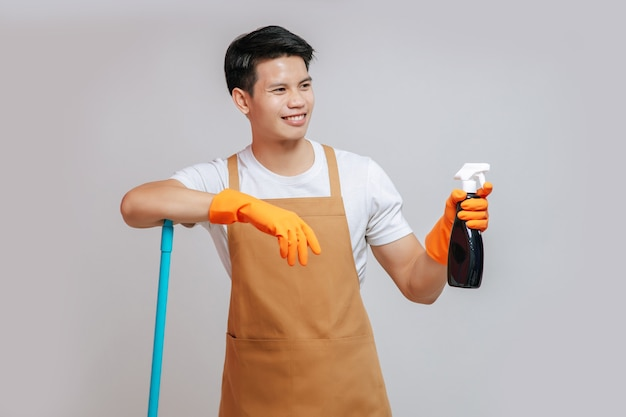 Portret gelukkige knappe man in schort en rubberen handschoenen, staande glimlach en poseren met een spuitfles die zich voorbereidt op het schoonmaken, kopieer ruimte