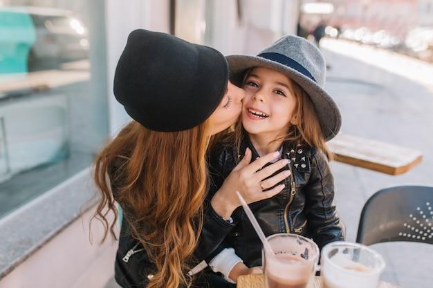 Portret gelukkige liefdevolle familie samen. moeder en haar dochter zitten in een stadscafé en spelen en knuffelen. gelukkig meisje dat de camera bekijkt, moeder die dochter op de wang kust.