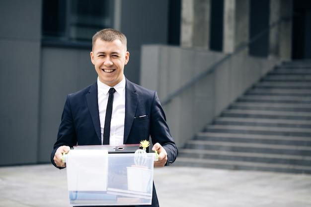 Portret gelukkige mannelijke beambte met doos met persoonlijke spullen