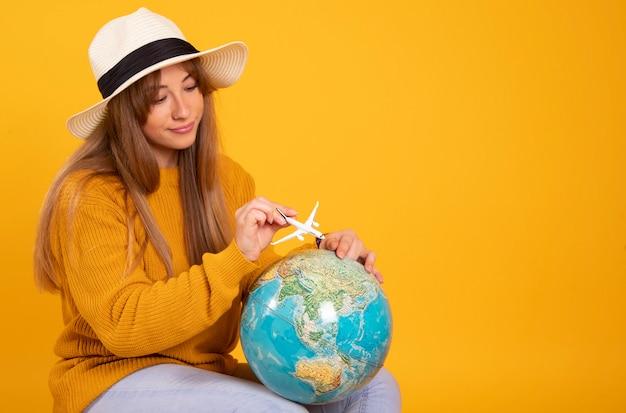 Portret gelukkige vrouw, reiziger met een wereldbol en koffer, op gele ruimte