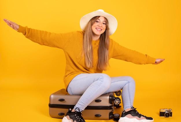 Portret gelukkige vrouw, reiziger met hoed en koffer, op gele ruimte
