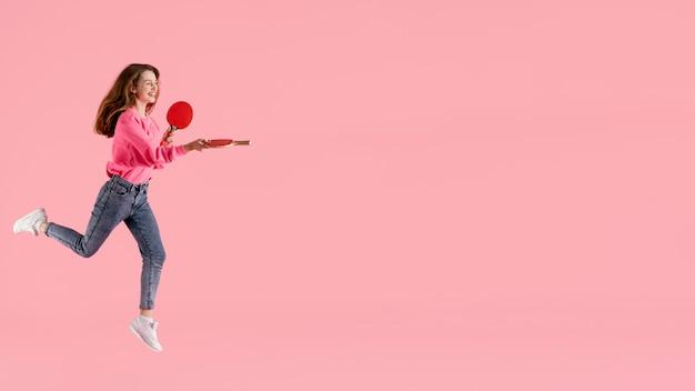 Portret gelukkige vrouw springen met pingpongpeddel
