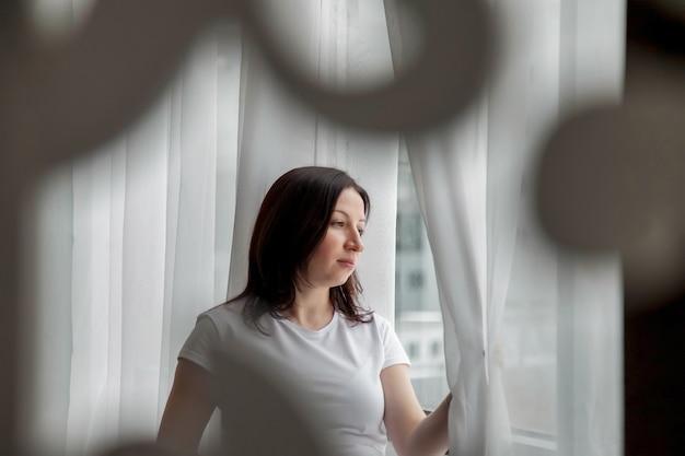 Portret gelukkige zwangere vrouw met grote buik bij raam in huis. zwangerschap, moederschap, mensen en verwachtingsconcept. sfeervolle familiemomenten. ruimte kopiëren