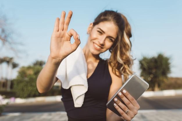 Portret gemotiveerde opgewonden gelukkige jonge vrouw in sportkleding glimlachen, positiviteit uitdrukken in zonnige ochtend buiten. modieuze sportvrouw, training, gezonde levensstijl
