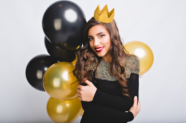 Portret geweldig mooi meisje met lang krullend donkerbruin haar, gele kroon, zwarte en gouden ballonnen op witte ruimte.