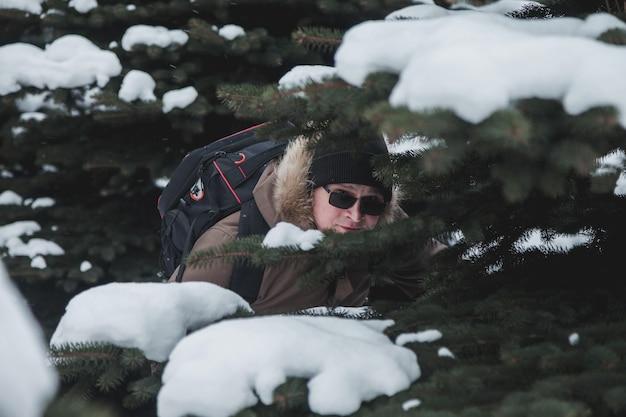 Portret glimlachend brutale jonge man in open lucht tussen besneeuwde kerstbomen in het winterseizoen in het bos. toerist met bril en rugzak verdwaald in een onbekend gebied. tiener gekke wandelingen