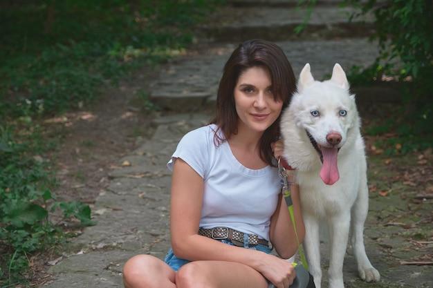 Portret glimlachende vrouw en comfortabele hond met uit tong, stellend terwijl het zitten en het kijken