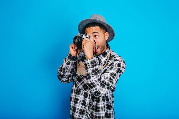 Portret grappige opgewonden toeristenkerel in hoed die foto op camera maakt. plezier hebben, genieten van vakanties, weekenden, de wereld rondreizen, positiviteit uiten.