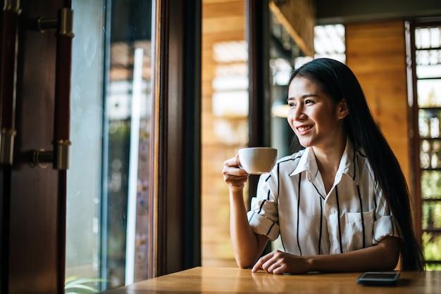 Portret het aziatische vrouw glimlachen ontspant in de koffie van de koffiewinkel