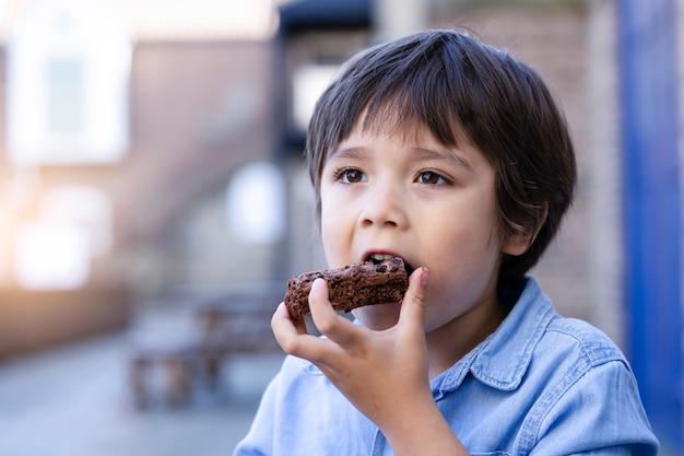 Portret hugry jongetje geniet van het eten van chocoladetaart in openlucht café met onscherpe achtergrond van mensen, kid eet snack na het spelen in het park, kind eet voedsel met lekker gezicht
