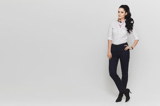 Portret in de volle lengte van een jonge vrouw in witte blouse en in donkere broek geïsoleerd op witte muur. kopieer ruimte aan de linkerkant