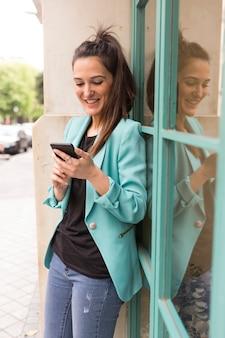 Portret in openlucht van jonge gelukkige bloggervrouw met mobiele telefoon. glazen ramen achtergrond. vrijetijdskleding dragen. plezier en levensstijl
