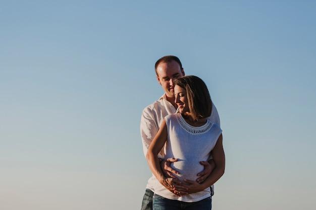 Portret in openlucht van jonge jonge zwanger. zonsondergang en blauwe lucht. buitenshuis familie levensstijl.