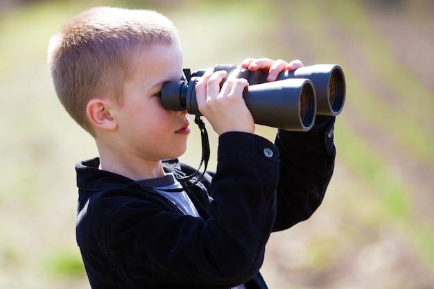 Portret in profiel van weinig knappe leuke blonde jongen die th kijken
