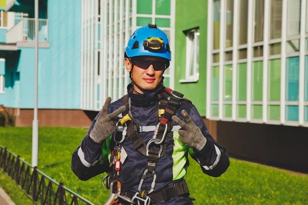 Portret industriële alpinisme werknemer residentiële gevel gebouw tijdens het wassen van de buitengevel beglazing. kabeltoegangsarbeider bij muur van huis. concept van stedelijke werken. ruimte voor site kopiëren