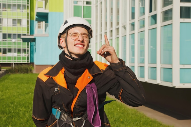 Portret industriële alpinisme werknemer residentiële gevel gebouw tijdens het wassen van de buitengevel beglazing. rope access arbeider hangt aan de muur van het huis. concept van stedelijke werken. ruimte voor site kopiëren