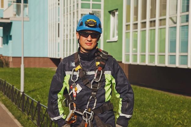 Portret industriële alpinisme werknemer residentiële gevel gebouw tijdens het wassen van de buitengevel beglazing
