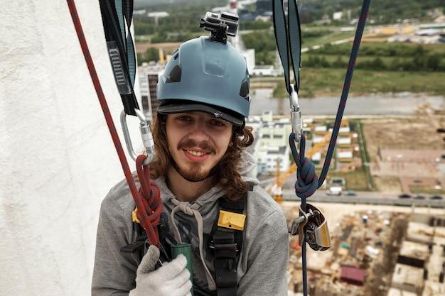 Portret industriële bergbeklimmer in uniform op dak woningbouw gevel tijdens hoogbouw werk. rope access arbeider op dak van huis. concept van industriële stedelijke werken. ruimte kopiëren