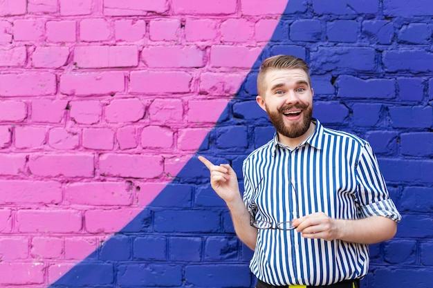 Portret is een aardige jonge studentenjongen met een snor en een baard die tegen een blauwviolette baksteen poseert