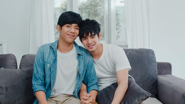 Portret jong aziatisch vrolijk paar die thuis gelukkig het glimlachen voelen. de aziatische lgbtq-mensen ontspannen toothy glimlach kijkend aan camera terwijl thuis het liggen op bank in woonkamer in de ochtend.