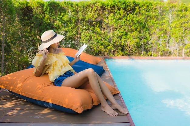 Portret jong aziatisch vrouw gelezen boek rond buitenzwembad