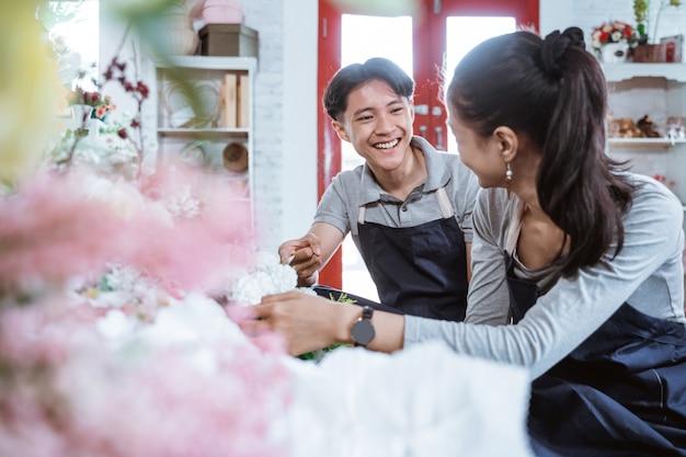 Portret jong koppel dragen schort glimlachend praten tijdens het samenwerken in bloemenwinkel