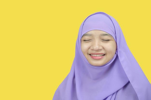 Portret jong meisje draagt paarse hijab op gele achtergrond.