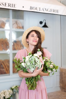 Portret jong meisje in jurk en strohoed met boeket bloemen tegen franse bakkerij