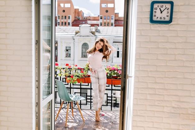 Portret jong meisje in pyjama verplaatsen op balkon in stad in zonnige ochtend. haar lange haren vliegen op de wind, ze glimlachte.