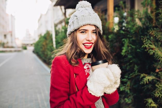 Portret jong meisje met lang haar in een rode jas lopen op straat. ze houdt koffie voor onderweg in witte handschoenen, glimlachend.