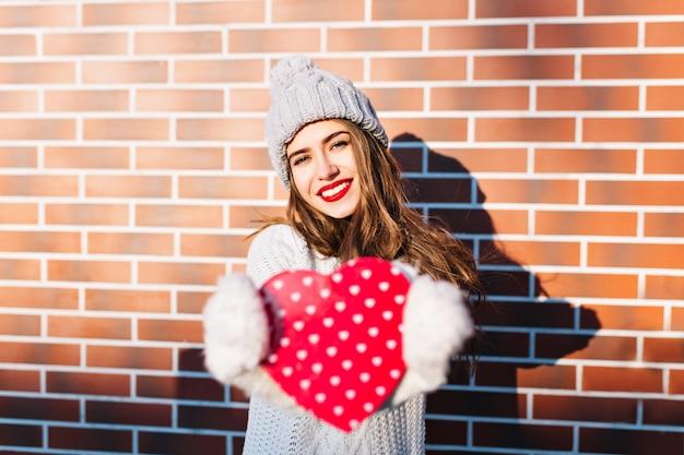 Portret jong meisje met lang haar in gebreide muts, warme trui op muur buiten. ze die zich uitstrekt rood hart in handschoenen.