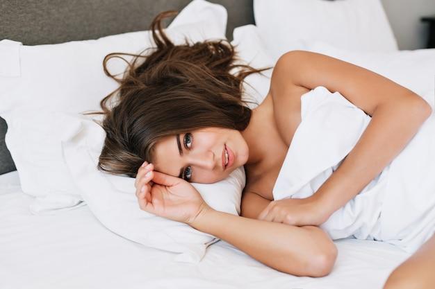 Portret jong meisje op bed in modern appartement in de ochtend. ze is aan het kijken .