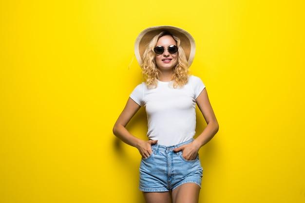 Portret jong mooi aantrekkelijk meisje glimlachend geïsoleerd op gele muur.