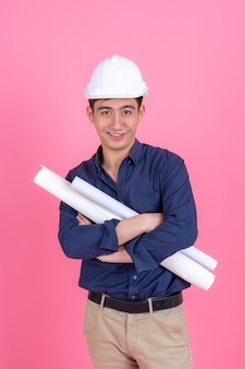 Portret jonge architect man dragen helm en houd blauwdruk