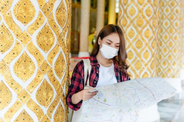 Portret jonge aziatische backpacker vrouw met masker staande en papieren kaart in de hand houden bij prachtige thaise tempel, ze zoekt richting looking