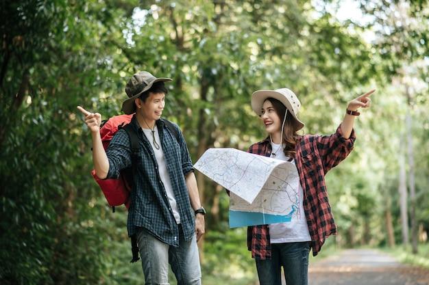 Portret jonge aziatische knappe man met rugzak en trekking hoed en mooie vriendin permanent en richting controleren op papieren kaart tijdens het wandelen op bospad, rugzak reizen concept