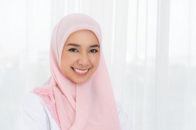 Portret jonge aziatische moslimvrouw in roze hoofddoek glimlach met kus verzenden.