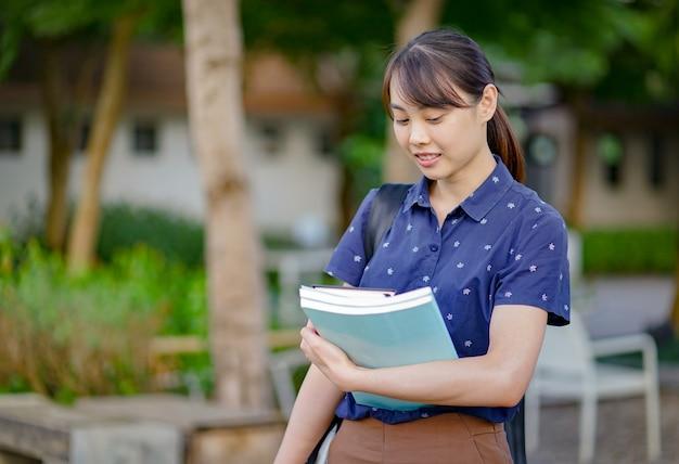 Portret jonge aziatische studentenvrouw die en boeken op haar wapen glimlacht houdt. onderwijs concept