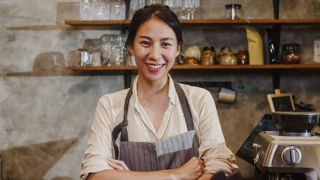 Portret jonge aziatische vrouw barista gelukkig lachend in stedelijke café.