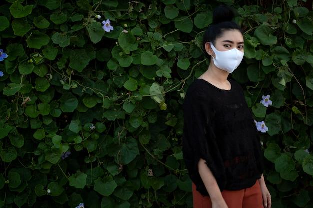 Portret jonge aziatische vrouw die en een maniermasker dragen dragen
