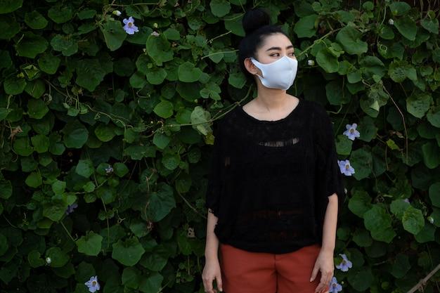 Portret jonge aziatische vrouw die en zich op een maniermasker bevinden zetten bij bladmuur Premium Foto