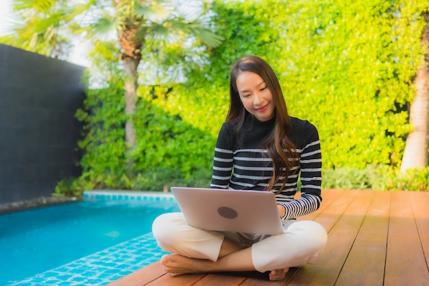 Portret jonge aziatische vrouw die laptop computer met behulp van rond openlucht zwembad