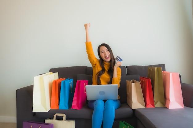 Portret jonge aziatische vrouw die laptop computer met slimme mobiele telefoon en creditcard voor online het winkelen met behulp van