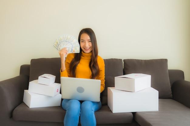 Portret jonge aziatische vrouw die laptop computer voor het werk met pakketdoos met behulp van
