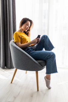 Portret jonge aziatische vrouw die mobiele telefoon gebruikt, zit op een stoel in het interieur van de woonkamer