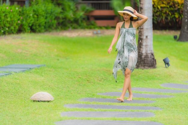Portret jonge aziatische vrouw die op wegmanier lopen in de tuin