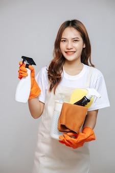 Portret jonge aziatische vrouw in schort en rubberen handschoenen, glimlach en schoonmaakapparatuur in haar hand, kopieer ruimte
