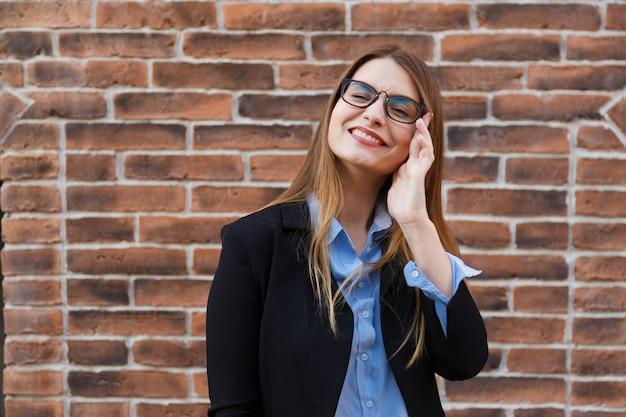 Portret jonge beambte vrouw in pak en bril op bakstenen muur