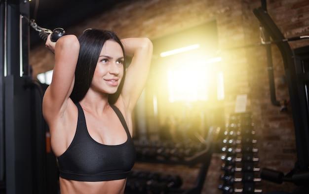 Portret jonge brunette fit vrouw uitvoeren oefening voor triceps met hometrainer cable crossover in de sportschool. trainingsproces
