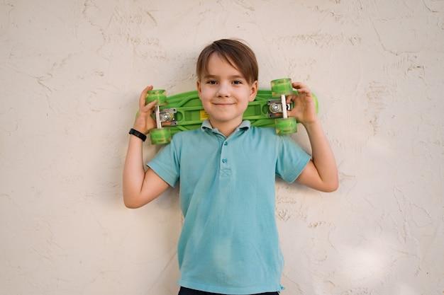 Portret jonge coole lachende jongen in blauwe polo poseren met penny board in de handen